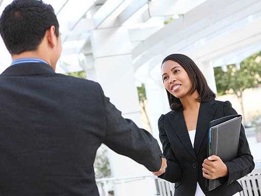 A man in a dark colored suit shakes hands with a smiling woman in a black blazer as she holds a folder in her left hand.