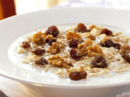 White bowl of oatmeal topped with raisins and walnuts.