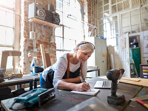 Woman with light blond hair leans over a workshop desk and writes in a notebook.