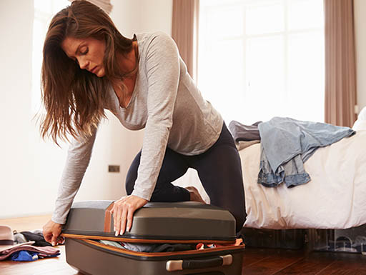 Woman packing clothes in suitcase with difficulty