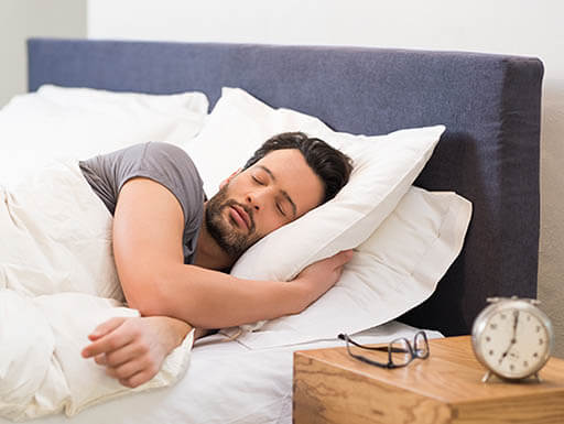 Man sleeping under a large white comforter, with alarm clock and glasses on nightstand beside him.