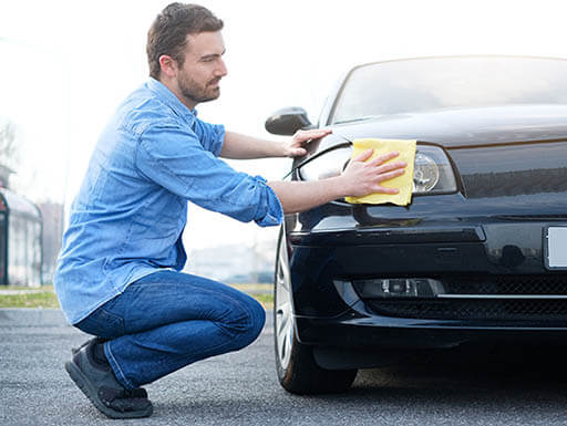 Man in denim kneels to wipe front passenger side headlight on black car with a yellow cloth.