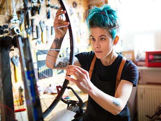 Woman with spiky blue hair fixes a bicycle tire in a shop.
