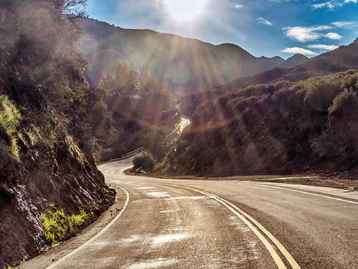 The famous Mulholland Highway showcasing it winding round through a ravine on a bright day in Malibu, California