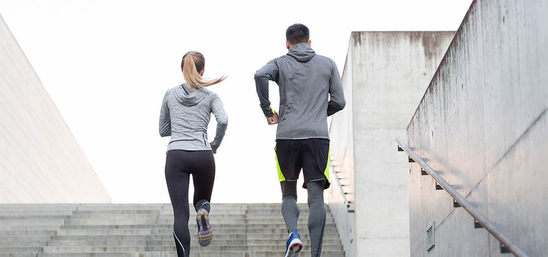 Young, healthy couple in fitness clothing jog together up staircase.