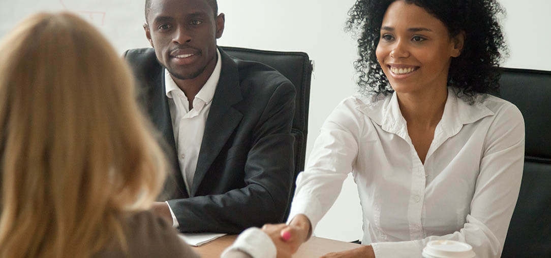 An African-American man and woman in business attire sit across the table from a woman with blonde hair. The two women are shaking hands.