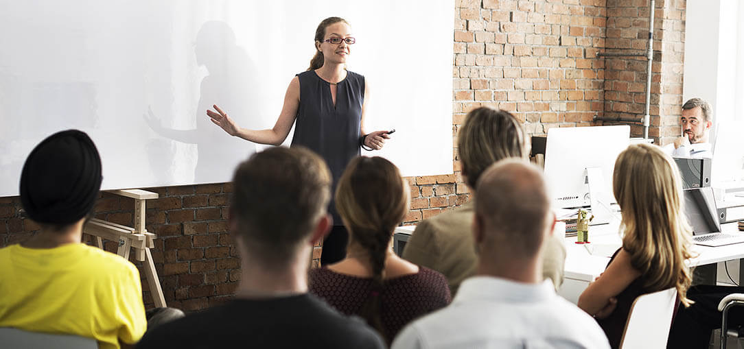 A woman with a ponytail and glasses stands in front of a whiteboard while speaking to a room full of men and women seated in chairs.