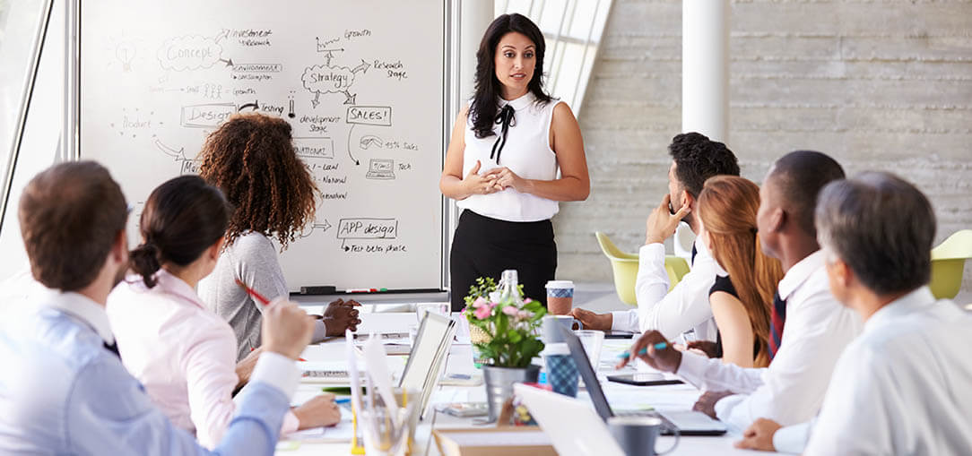 Hispanic businesswoman leading a meeting in front of a whiteboard.
