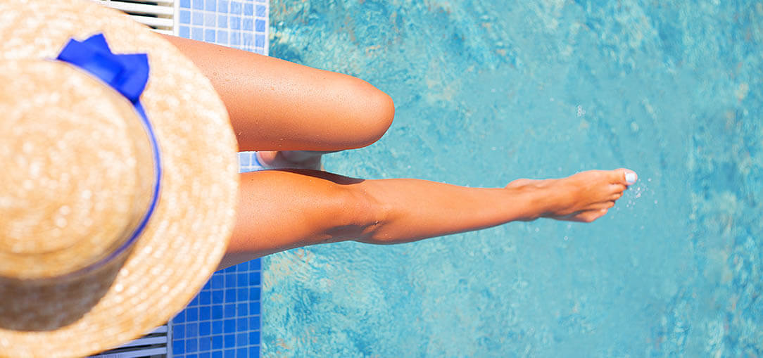 A photo from above of a woman in a large summer hat sitting on the edge of a pool with one leg outstretched and her foot dipped in the water, in Dallas, Texas on a hot summer morning