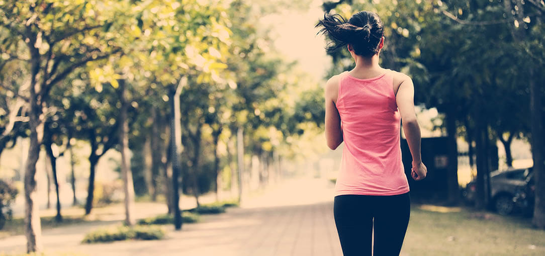 Young dark-haired woman in a pink tank top and black jogging pants running in a park.
