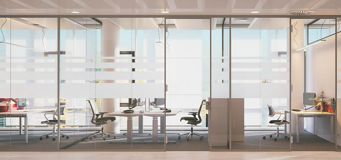 A modern, light-filled workspace features an entire wall of windows to the outside as well as glass walls separating several desks and conference rooms from a white-floored hallway.