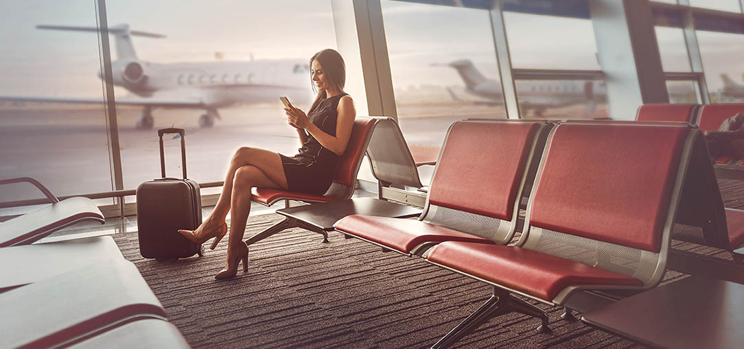 Happy young woman wearing black dress sits at airport gate.