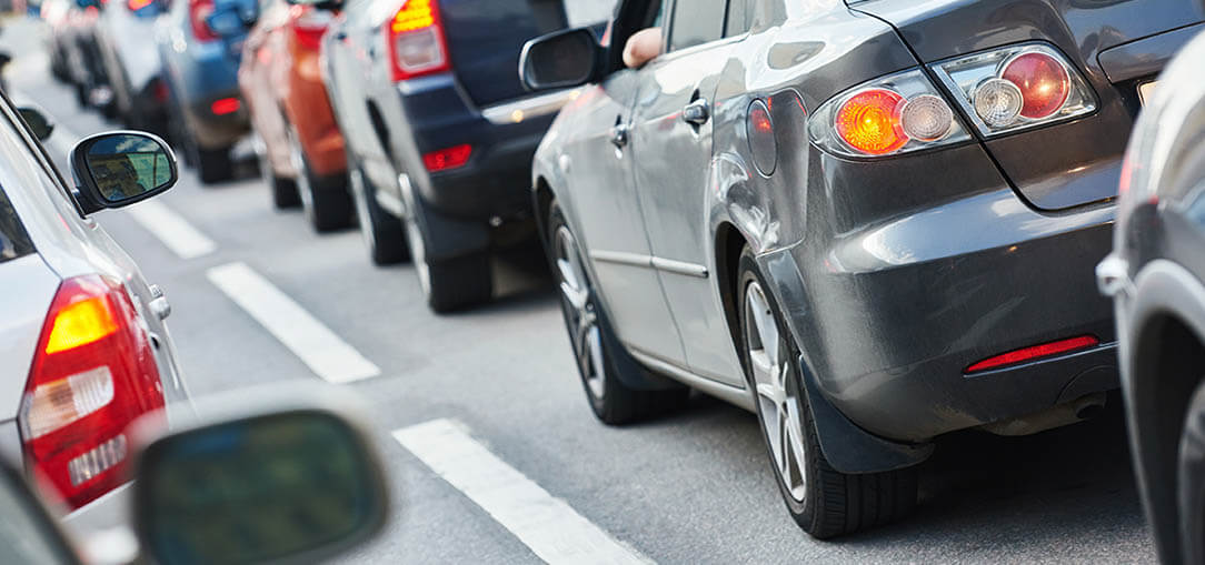The rears of a line-up of vehicles on a busy road.