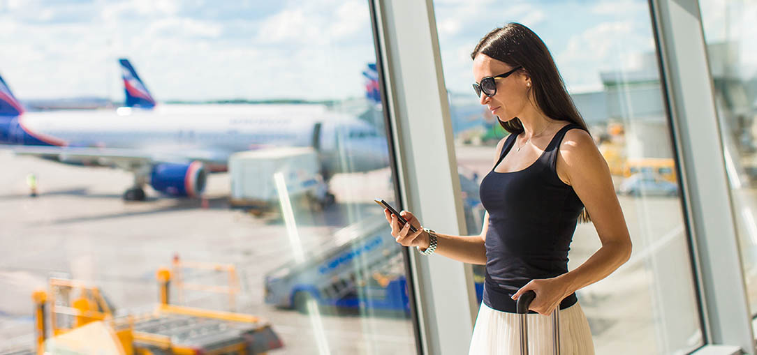 A young woman in business casual wear looks down at her phone with one hand on her suitcase handle while standing in front of a large window at an airport with airplanes in the background as she travels for business.