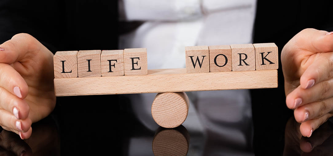 """Hands holding wooden letter tiles reading """"life"""" and """"work"""" balanced on roller."""