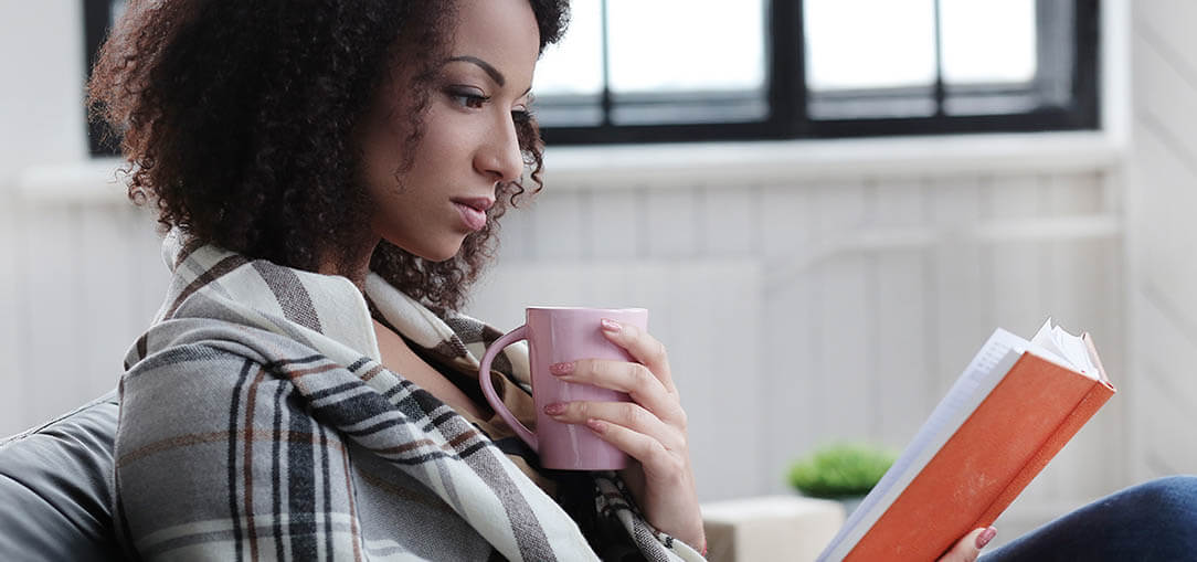A woman sits, while wrapped in a black and white plaid blanket, to read an orange-covered book while holding a pink coffee mug.