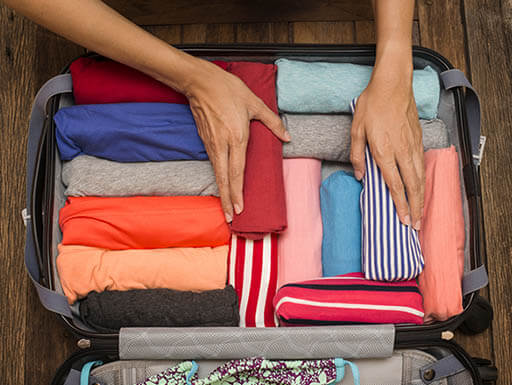 Overhead view of a woman packing a carryon suitcase with neatly rolled clothes perfectly organized.