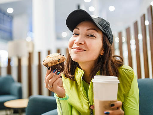 Young brunette woman enjoying a muffin and coffee with a smile on her face.