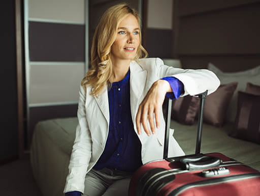 A businesswoman who has just arrived to her hotel room, sits on the bed with hand resting on suitcase while gazing out the window.