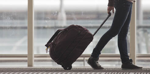 """=""""Woman pulling her luggage at an airport while talking on the phone."""