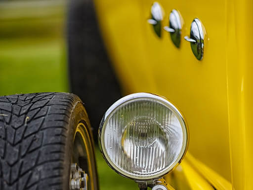Up close view of front headlight low to the ground next to tire of yellow 1932 Ford Phaeton