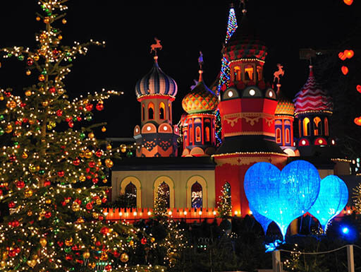 A brightly lit Christmas tree sits in the foreground of Tivoli Gardens in Copenhagen, Denmark at night, with the colorful amusement grounds buildings in the background