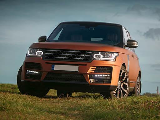 An orange Range Rover Sport parked on grass during the daytime.