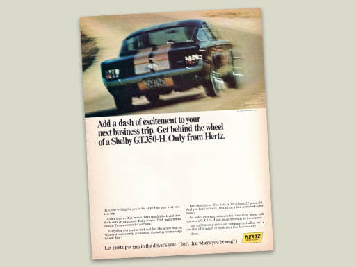 A Hertz ad from 1966 shows a Shelby Mustang GT 350-H on a race track with text that reads, 'Add a dash of excitement to your next business trip.