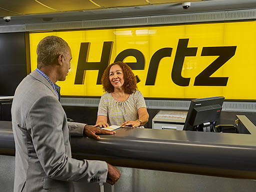 A businessman talks to a woman at a Hertz counter, both smiling as he reserves his car.