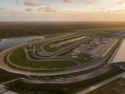 An aerial view of the full Homestead-Miami Speedway in Homestead, Florida, during sunset on a warm evening.