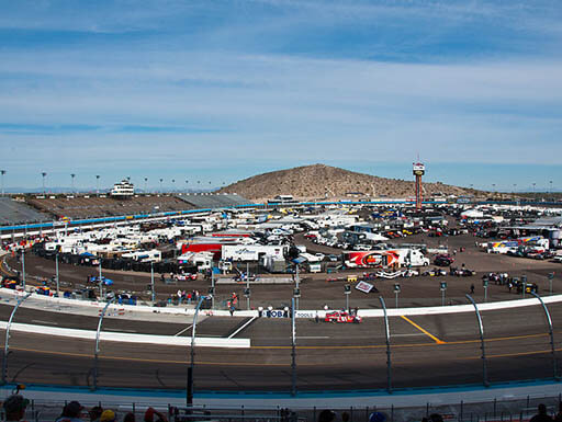 ISM Raceway is filled with racecars, fans, and drivers on a bright afternoon in 2011