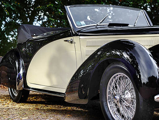 Black and cream colored convertible 1938 Buick Y-Job parked in front of trees on sunny day