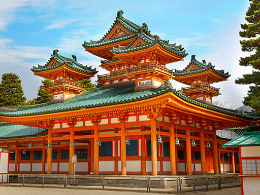 The beautiful orange and green Heian Jingu Shrine is one of many Shinto shrines in Kyoto, Japan, shown with a bright blue sky in the background.
