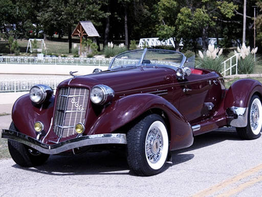 A dark purple Glenn Pray-designed Auburn 866 Speedster sits on the side of a road with a park and evergreen trees in the background