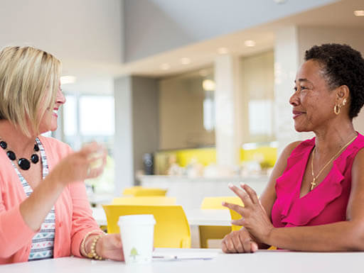 Two female employees meet in the open and bright cafeteria at Hertz corporate headquarters.