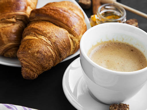 A plate topped with two breakfast croissants sits next to a cup of coffee with a side of honey on a bright morning.