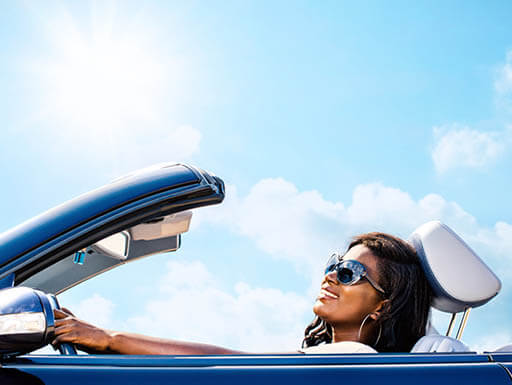 A woman wearing sunglasses while driving a blue convertible car on sunny