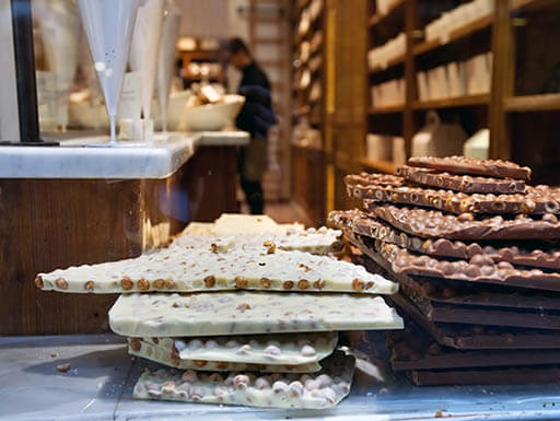 Stacks of white and milk chocolate slabs sit in the foreground of a chocolate shop in Brussels, Belgium