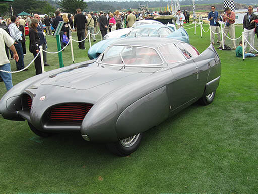 A silver Alfa Romeo BAT 7 concept car sits on display outside on grass, cordoned off with rope with spectators walking around it