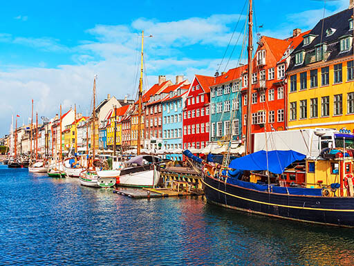 Various boats sit docked in a harbor in front of colorful yellow, orange blue and red homes in the Nyhavn Pier in Copenhagen, Denmark