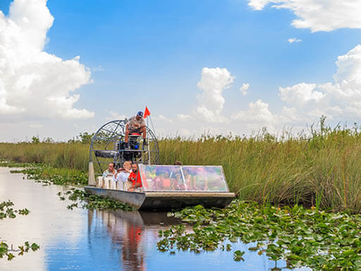 A group of tourists ride an airboat as they are led by their tour guide through the Everglades on a bright summer afternoon