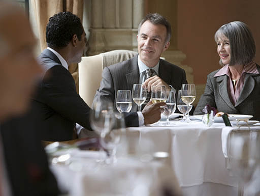 Two businessmen and a businesswoman talking at a restaurant table with water glasses and a white table cloth