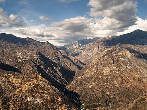 Aerial view of King's Canyon Park mountains under partly cloudy sky near sequoia national park in California