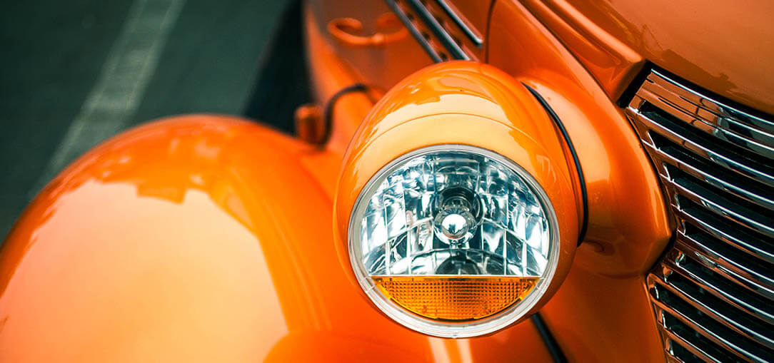Up close view of front headlight on orange 1930s car