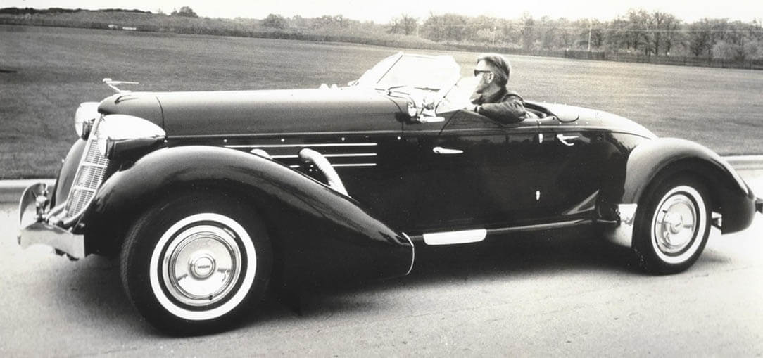 A black and white photo of Glenn Pray in his restored 1936-1937 Auburn Cord Phaeton, on a road with open fields in the background
