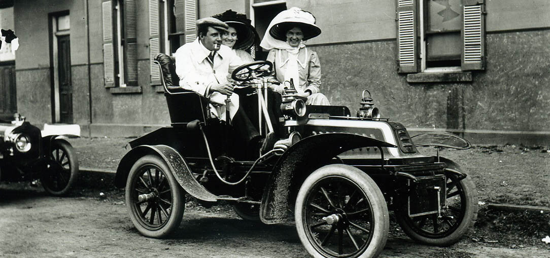 Black and white photo of 3 people in a 1908 motor car