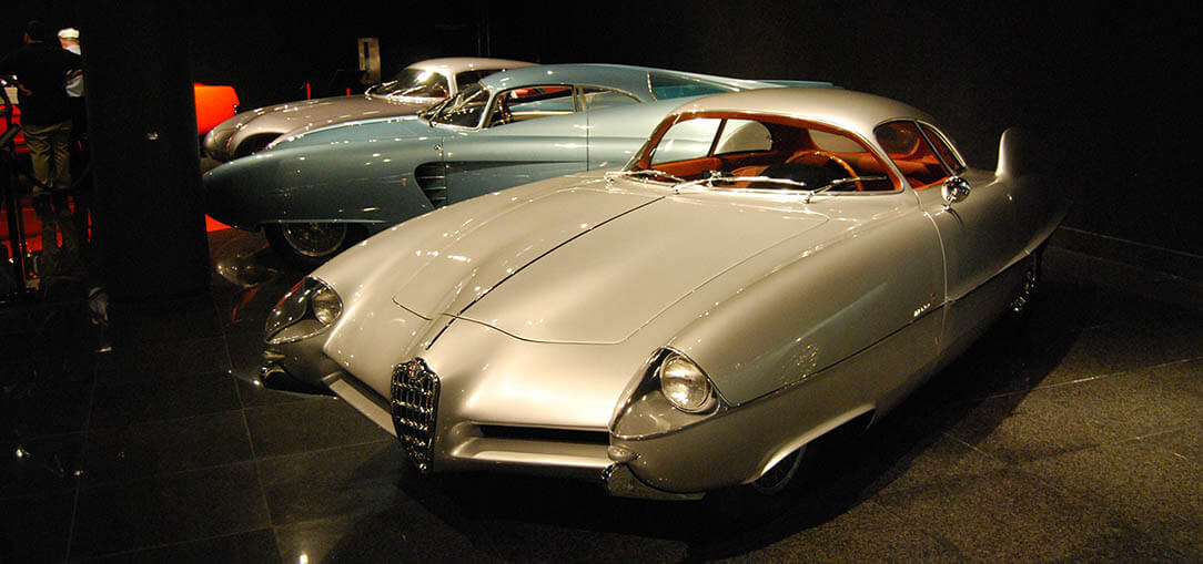 A bronze Alfa Romeo BAT concept car sits on display with the other two BAT models in the Blackhawk Museum in Danville, California