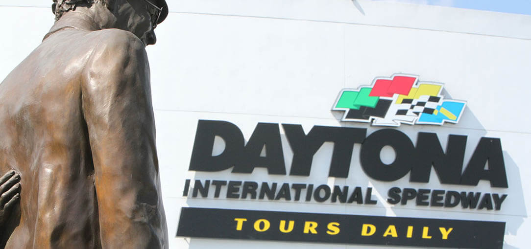 The back of the Dale Earnhart Senior statue is pictured with the Daytona International Speedway sign behind it in Daytona Beach, Florida, on a bright morning.