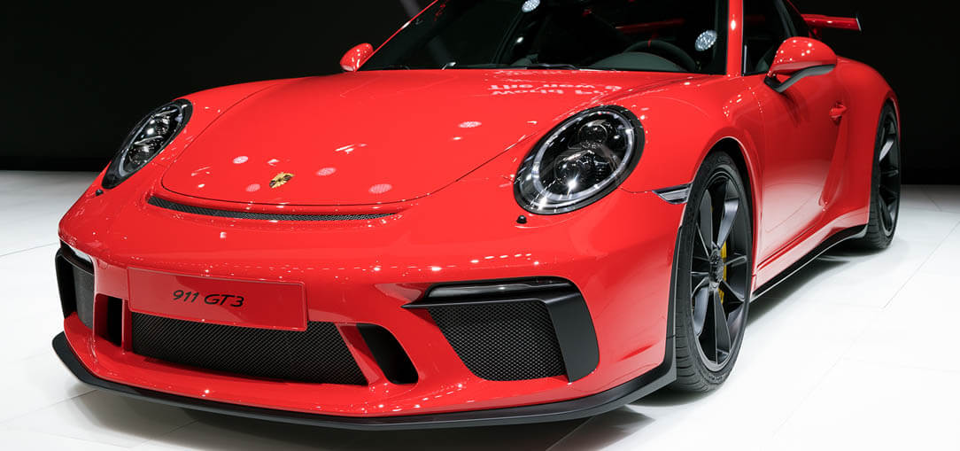 A red Porsche 911 parked in a showroom with dramatic lighting.