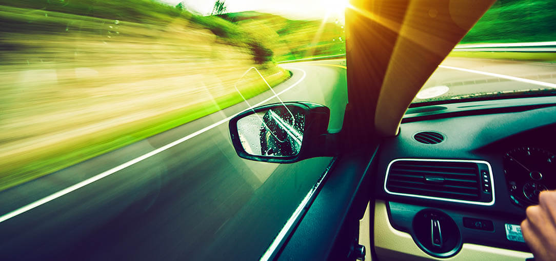 A driver travels along a road into the sunlight